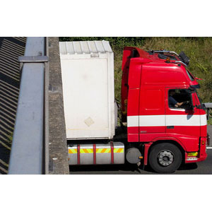 BK9AG1 Cyclist on a pedestrian / cycle / footbridge looks down on lorry / traffic travelling on M25 motorway nr Leatherhead. Surrey, UK. Image shot 2011. Exact date unknown.
