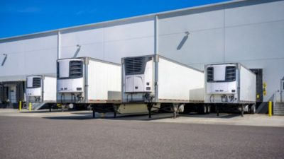 Four refrigeration units being loaded